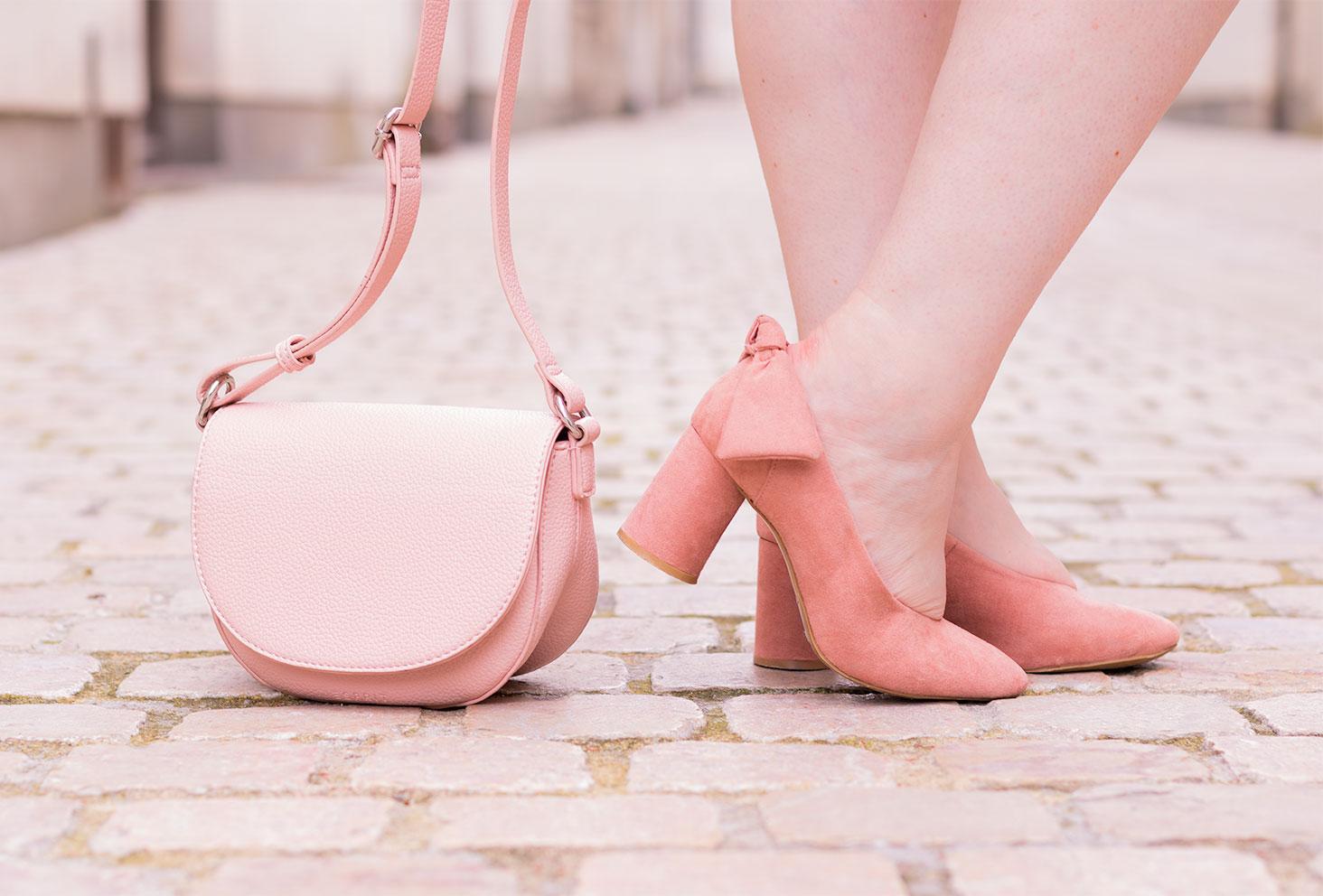Zoom sur les escarpins roses à nœuds Kiabi porté et sur la pochette rose Esprit posé sur le sol à côté