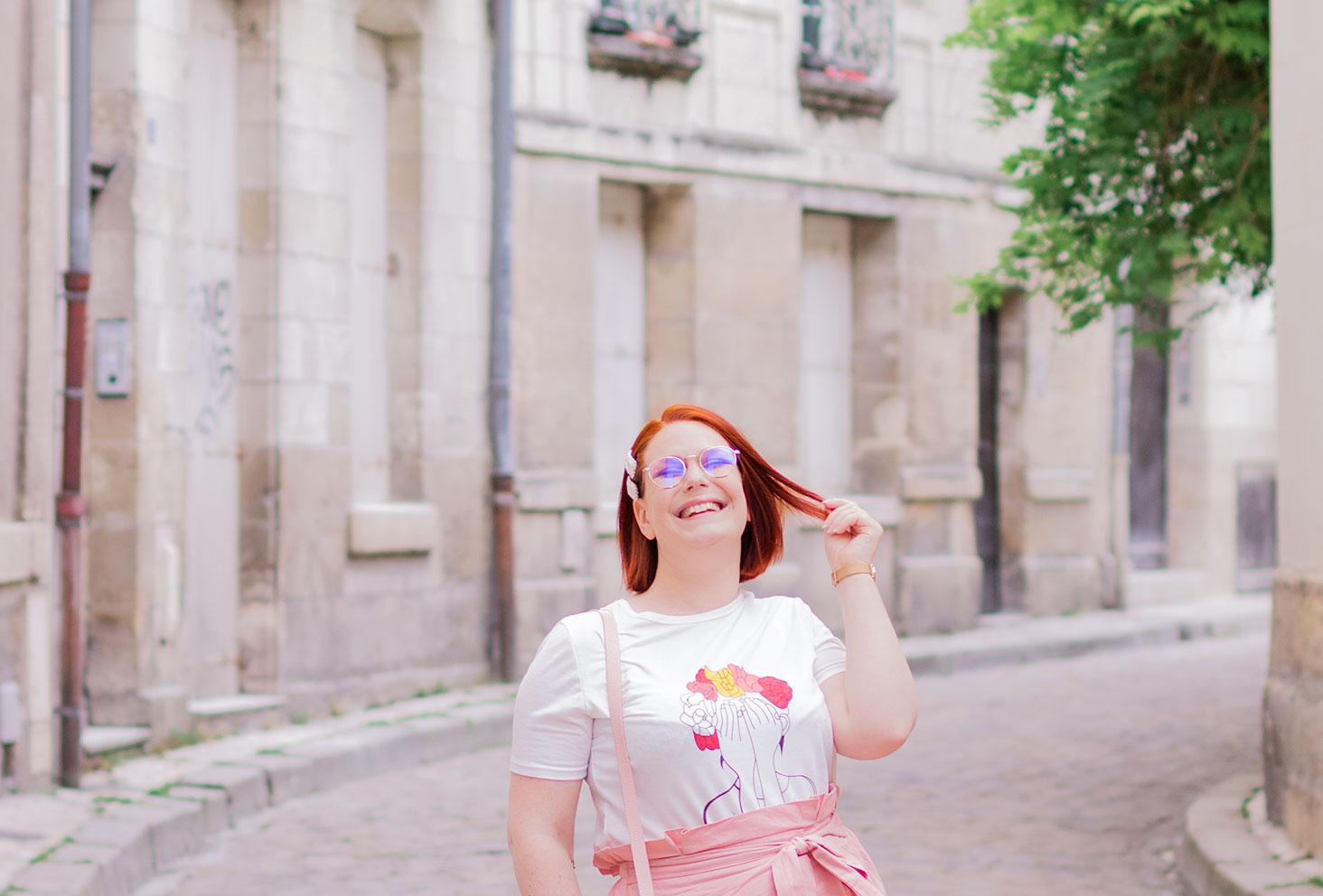 Zoom sur le t-shirt à motif visage de femme et fleurs roses Shein porté dans la rue, une main dans les cheveux avec le sourire