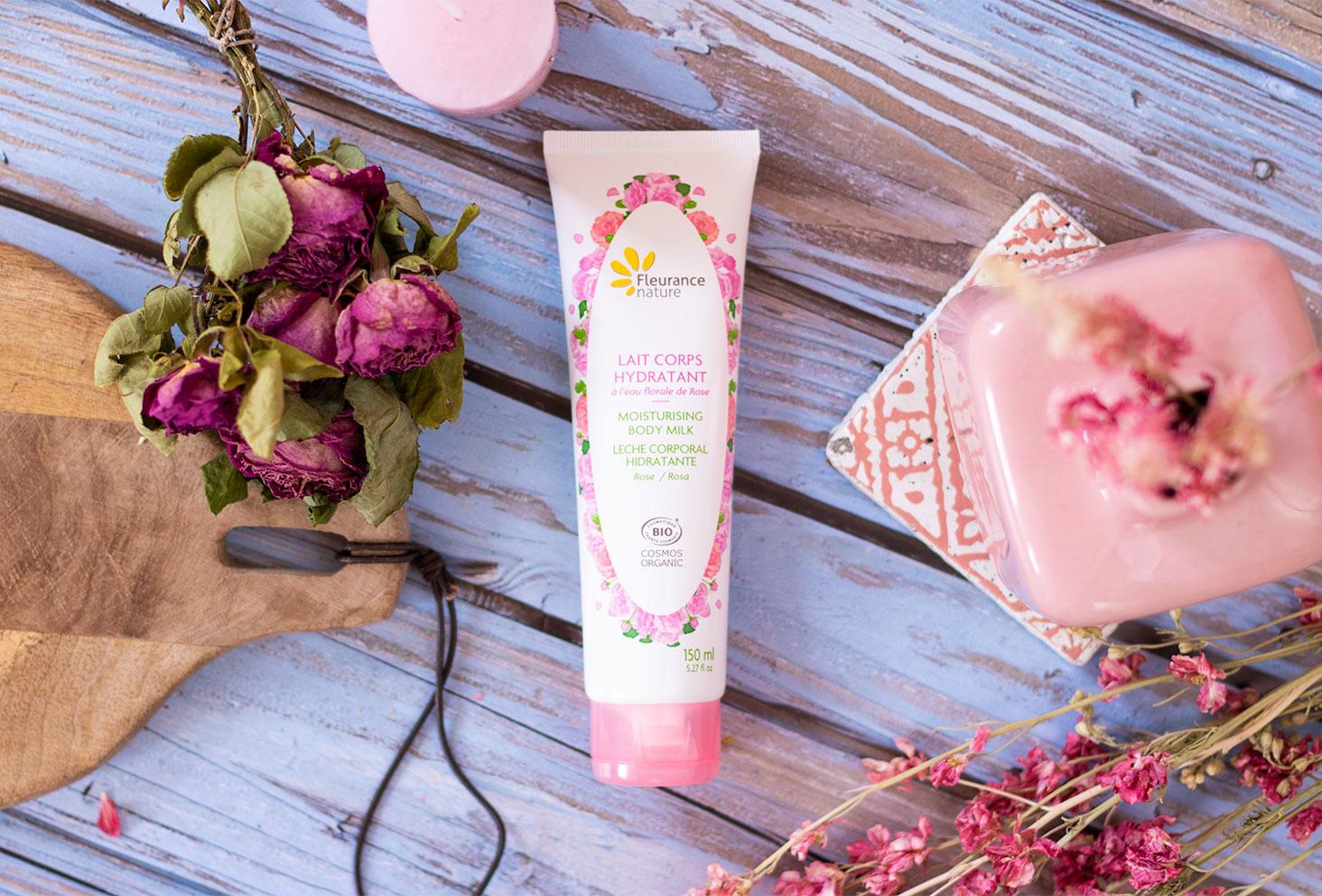Zoom sur la crème hydratante pour le corps à la rose de Fleurance Nature sur un parquet de plage bleu, vue de haut au milieu de fleurs séchées roses à côté d'une planche en bois