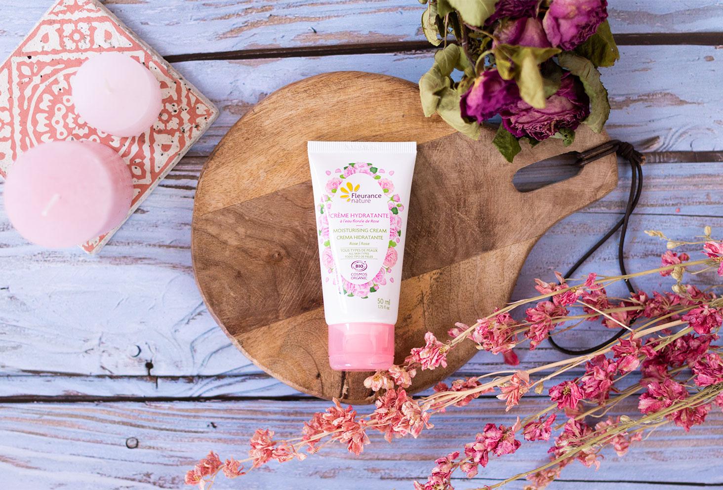 Zoom sur la crème hydratante pour le visage à la rose de Fleurance Nature, sur une planche à découper posée sur un parquet de plage bleu, vue de haut au milieu de fleurs séchées roses