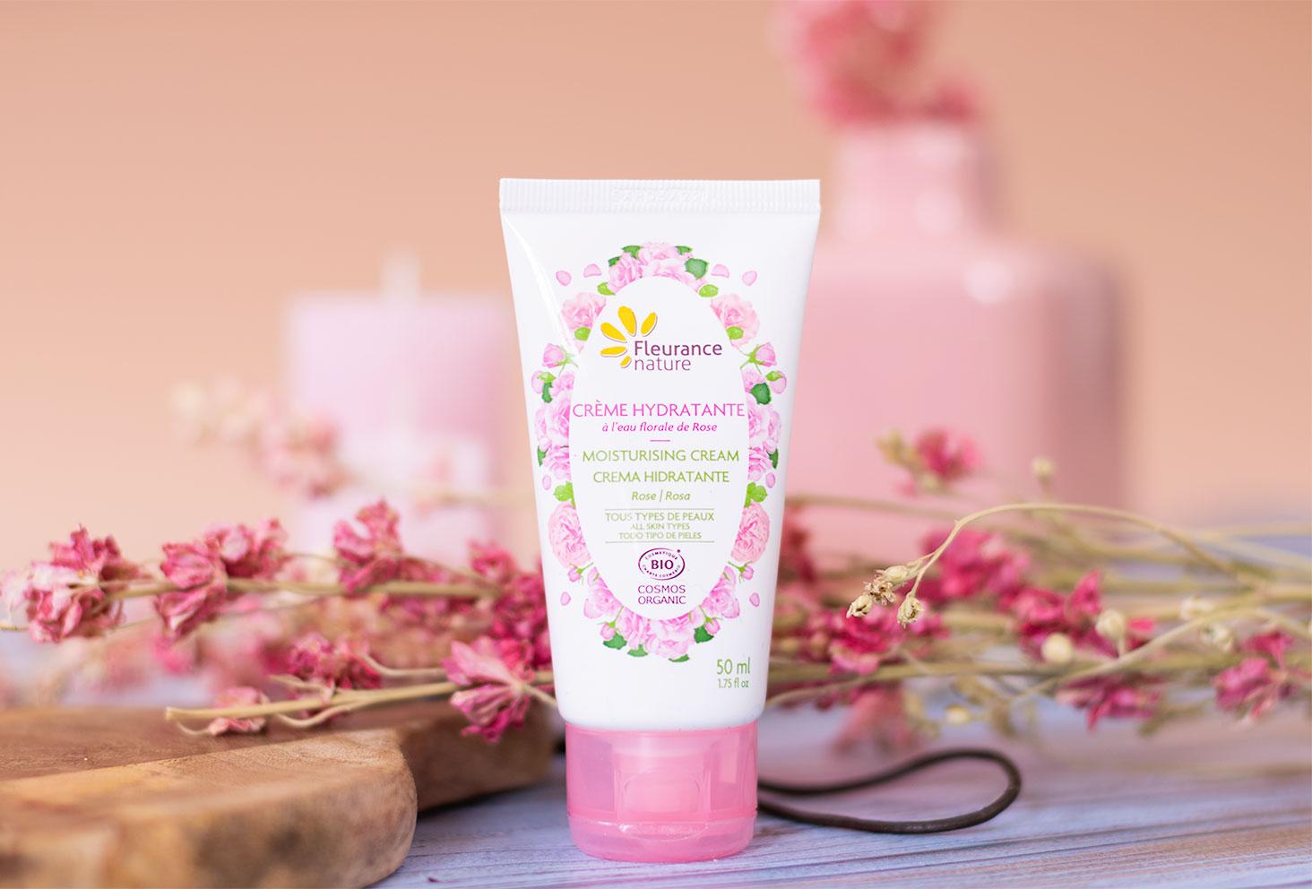 La crème hydratante BIO pour le visage de Fleurance Nature, debout devant une planche à découper en bois et des fleurs séchées roses