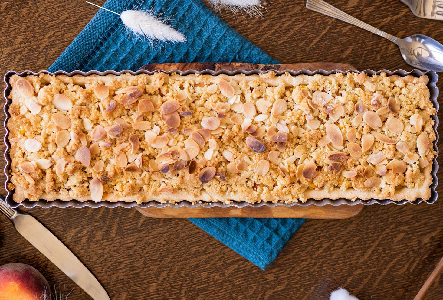 Zoom de haut sur la tarte crumble aux pêches et amandes, dans un plat rectangulaire sur un torchon bleu canard