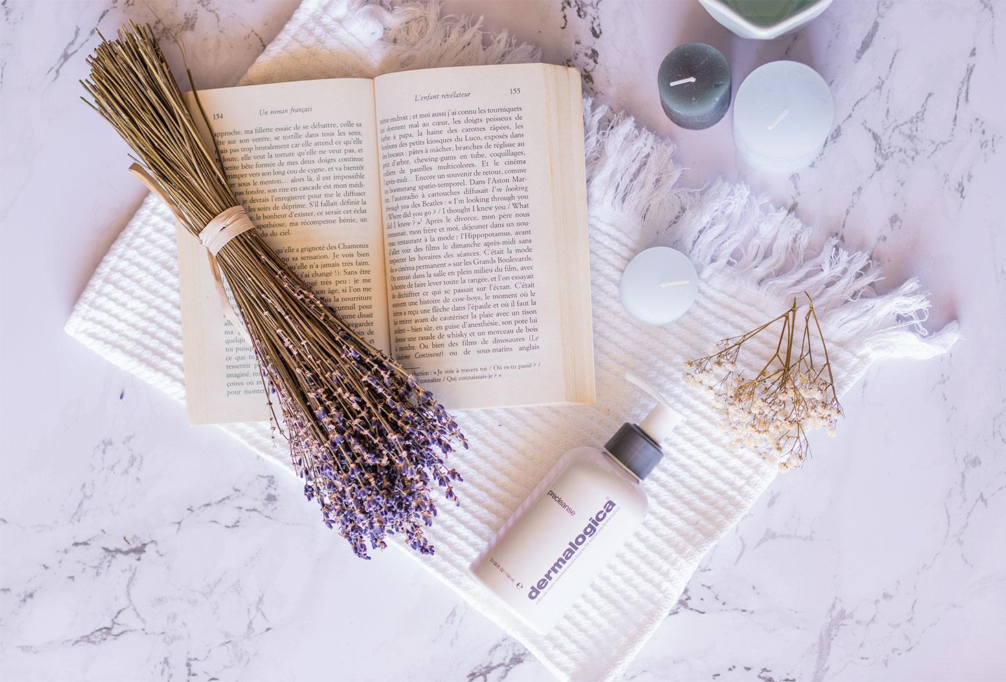 Le démaquillant Precleanse de Dermalogica sur une serviette blanche avec un livre ouvert et un bouquet de Lavande, posé sur du marbre avec quelques bougies