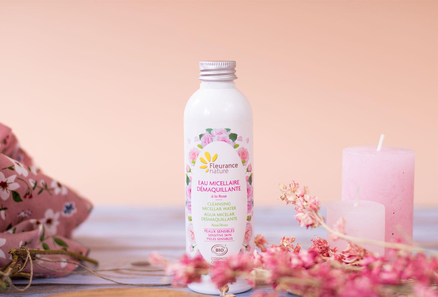 L'eau micellaire BIO pour le visage de Fleurance Nature, à côté d'une planche à découper en bois, de fleurs séchées roses et de bougies roses