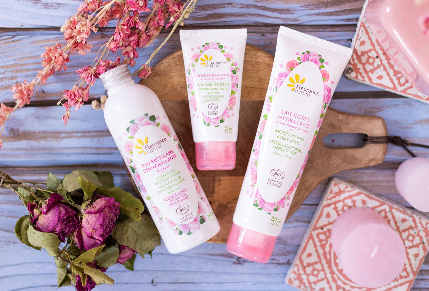 La gamme à la rose de Fleurance Nature de haut, posée sur une planche à découper en bois au milieu de bougies et fleurs séchées roses