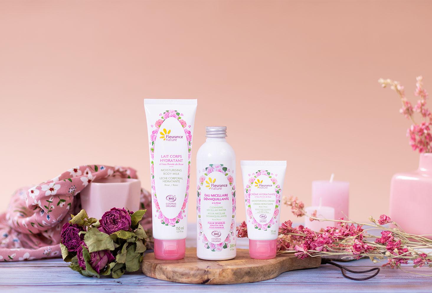 Les produits à la rose de Fleurance Nature debout sur une planche à découper, devant des fleurs roses séchées et des bougies