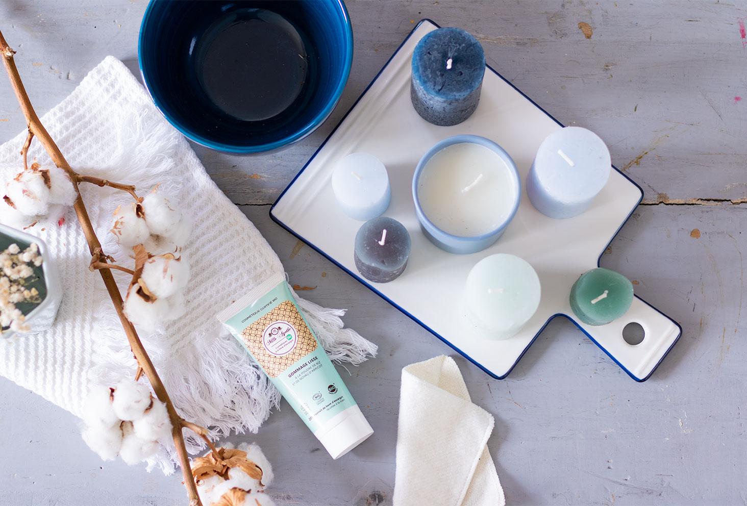 Le gommage visage de Mlle Agathe de haut et de loin, sur une table vintage bleue à côté de plusieurs bougies dans une salle de bain