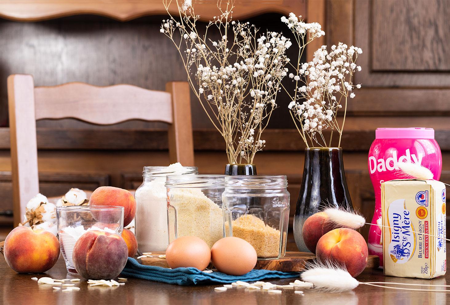Les ingrédients nécessaires à la réalisation d'une tarte crumble aux pêches, posés sur une table en bois