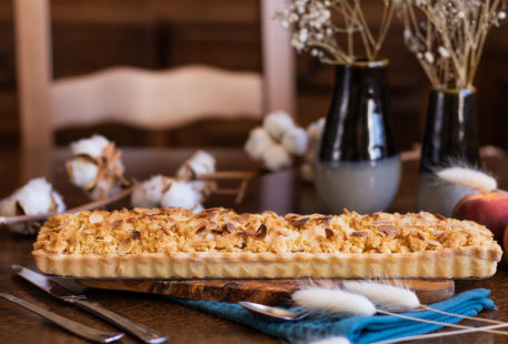 La tarte crumble aux pêches sur une planche à découper en bois foncé, sur un torchon bleu canard, au milieu de fleurs séchées et couverts en argent