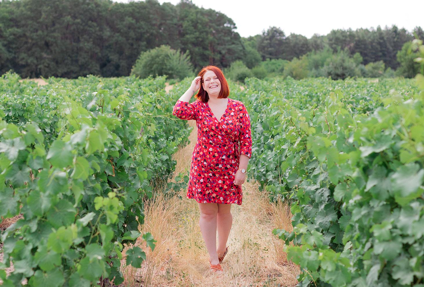 En robe rouge fleurie Grain de Malice au milieu des vignes, une main dans les cheveux avec le sourire