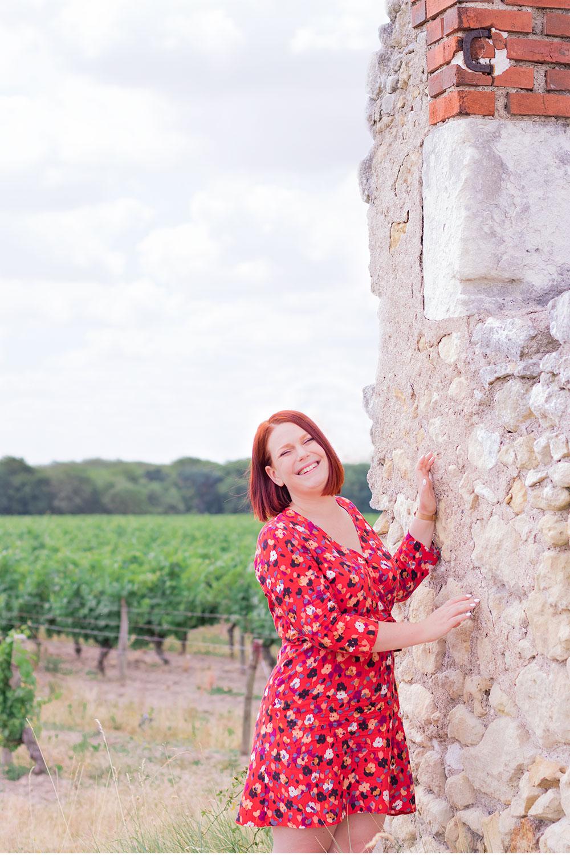 En robe rouge cache-coeur Grain de Malice, devant les vignes, accoudée le long des ruines d'une maison en pierre