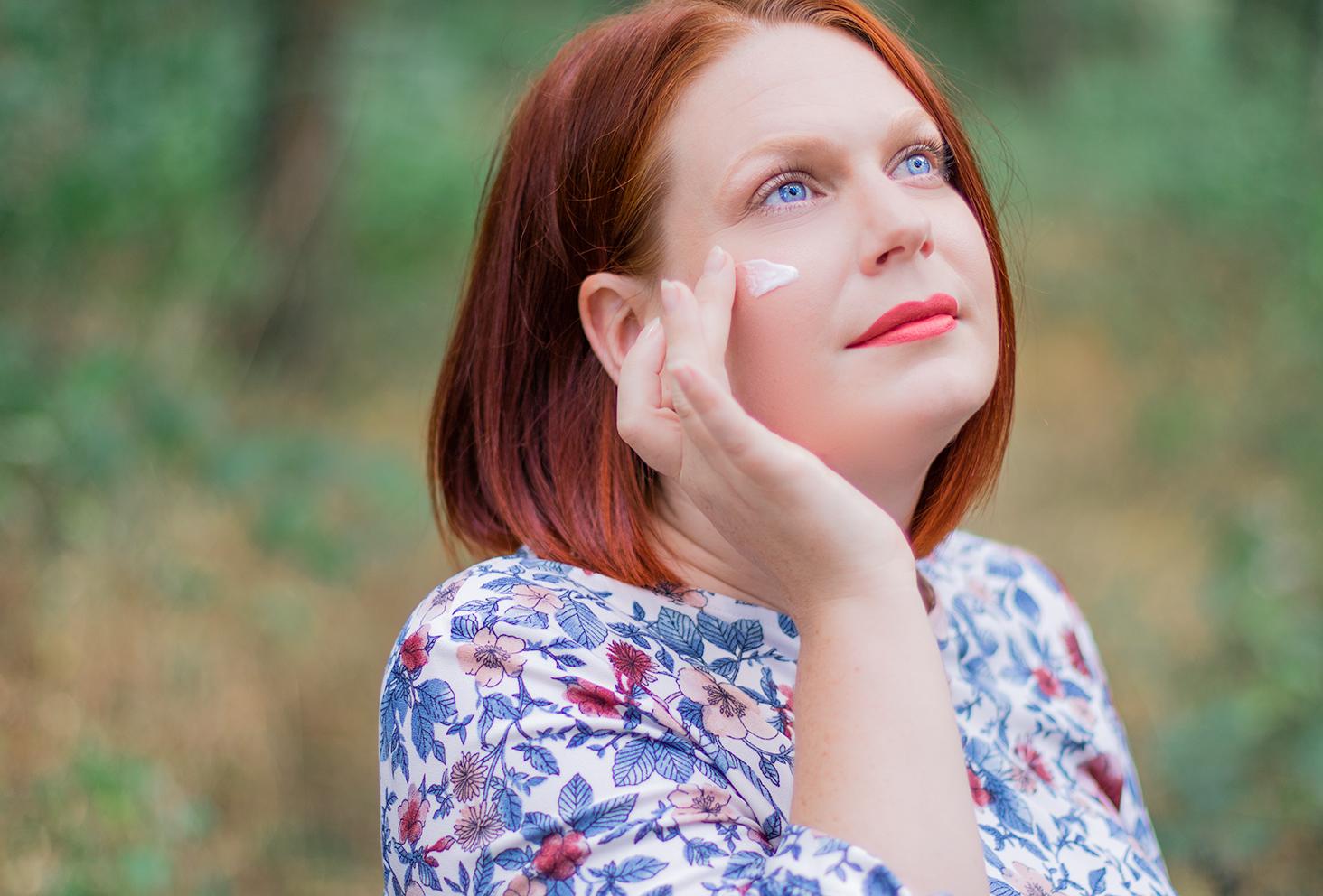 Application à l'aide des doigts d'une crème sur le visage pour la routine visage idéale pour l'été