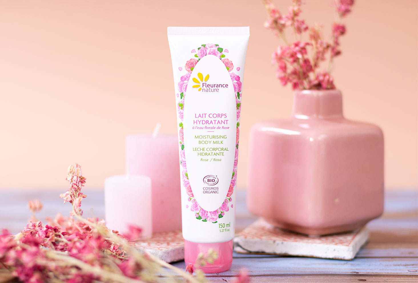 Le lait hydratant BIO pour le corps de Fleurance Nature, au milieu de fleurs séchées roses et de bougies