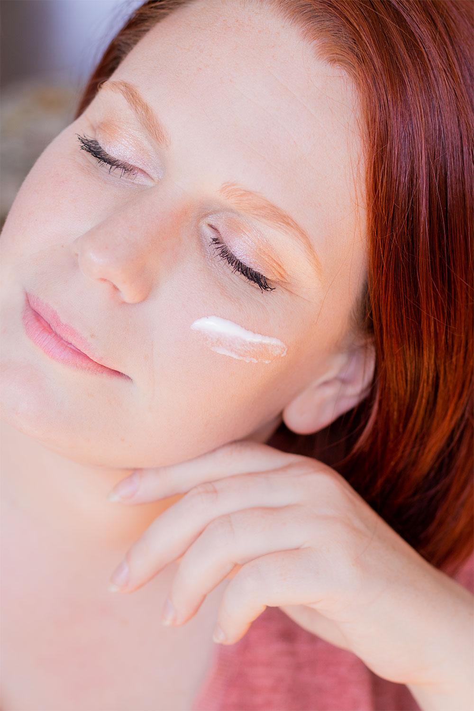 Zoom sur la texture de la crème hydratante pour le visage, sur la joue de profil les yeux fermés