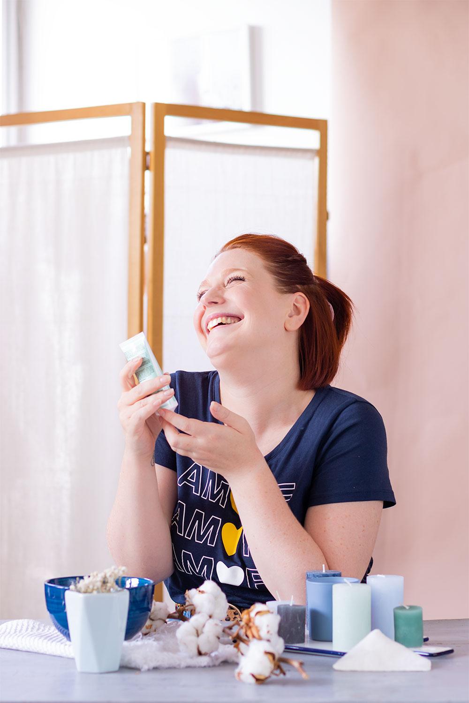 Utilisation du gommage pour le visage de Mlle Agathe avec le sourire, appuyée sur une table en bois vintage, dans un décor de salle de bain