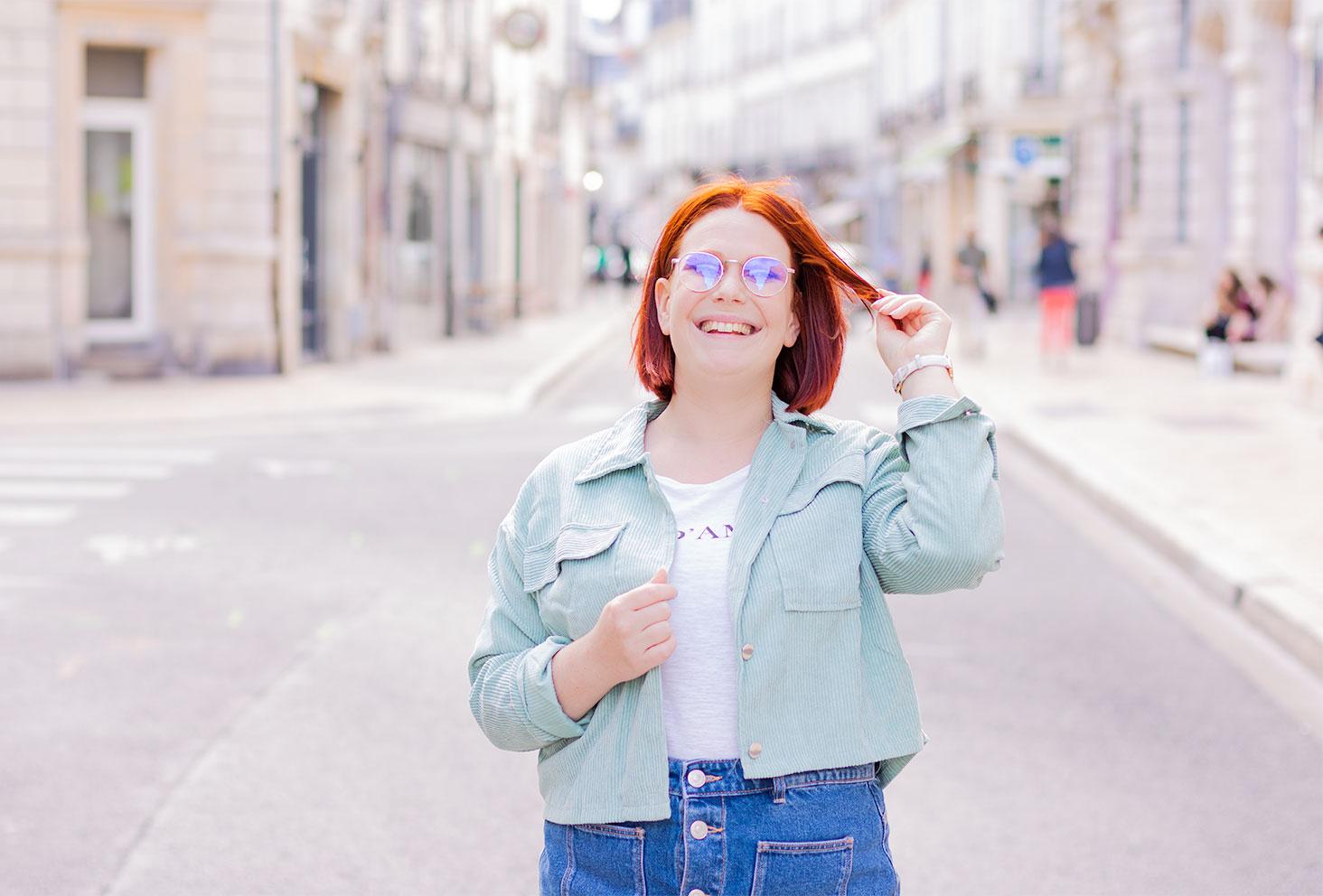 La veste en velours côtelé SheIn portée dans la rue avec une jupe en jean, la main dans les cheveux avec le sourire