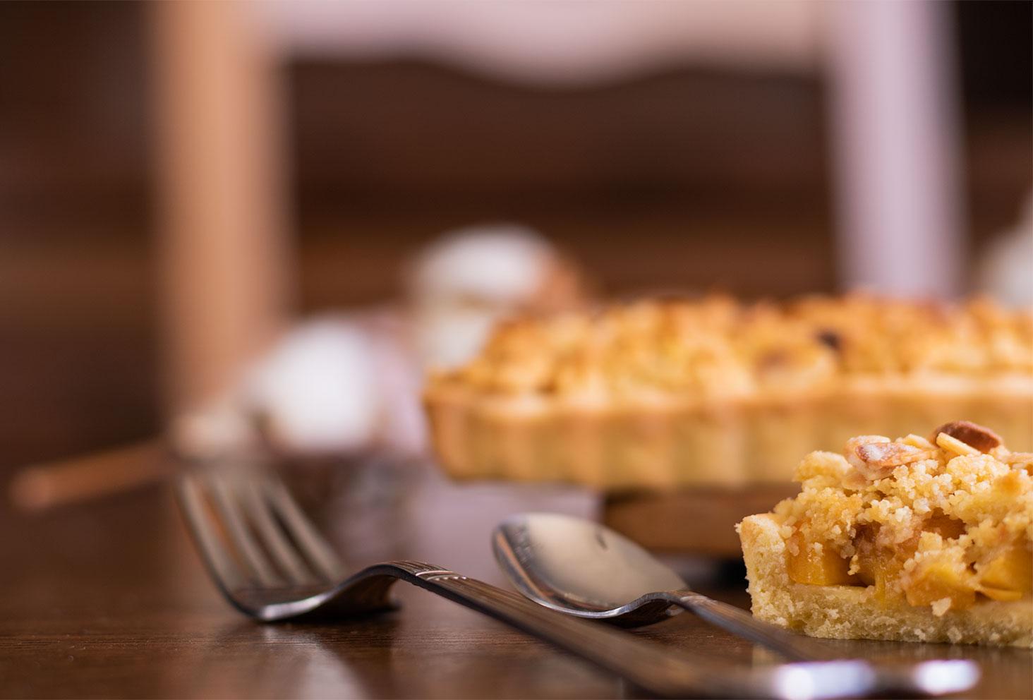 Sur une table, zoom sur une fourchette et une cuillère en argent, ainsi que sur une demi part de tarte crumble aux pêches