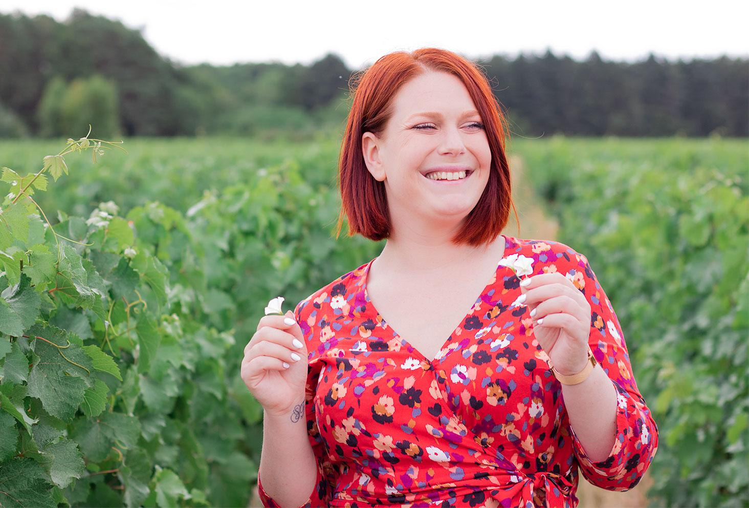 Zoom sur le décolleté cache-coeur de la robe rouge à fleurs Grain de Malice portée avec le sourire au milieu des vignes, des fleurs blanches dans chaque mains