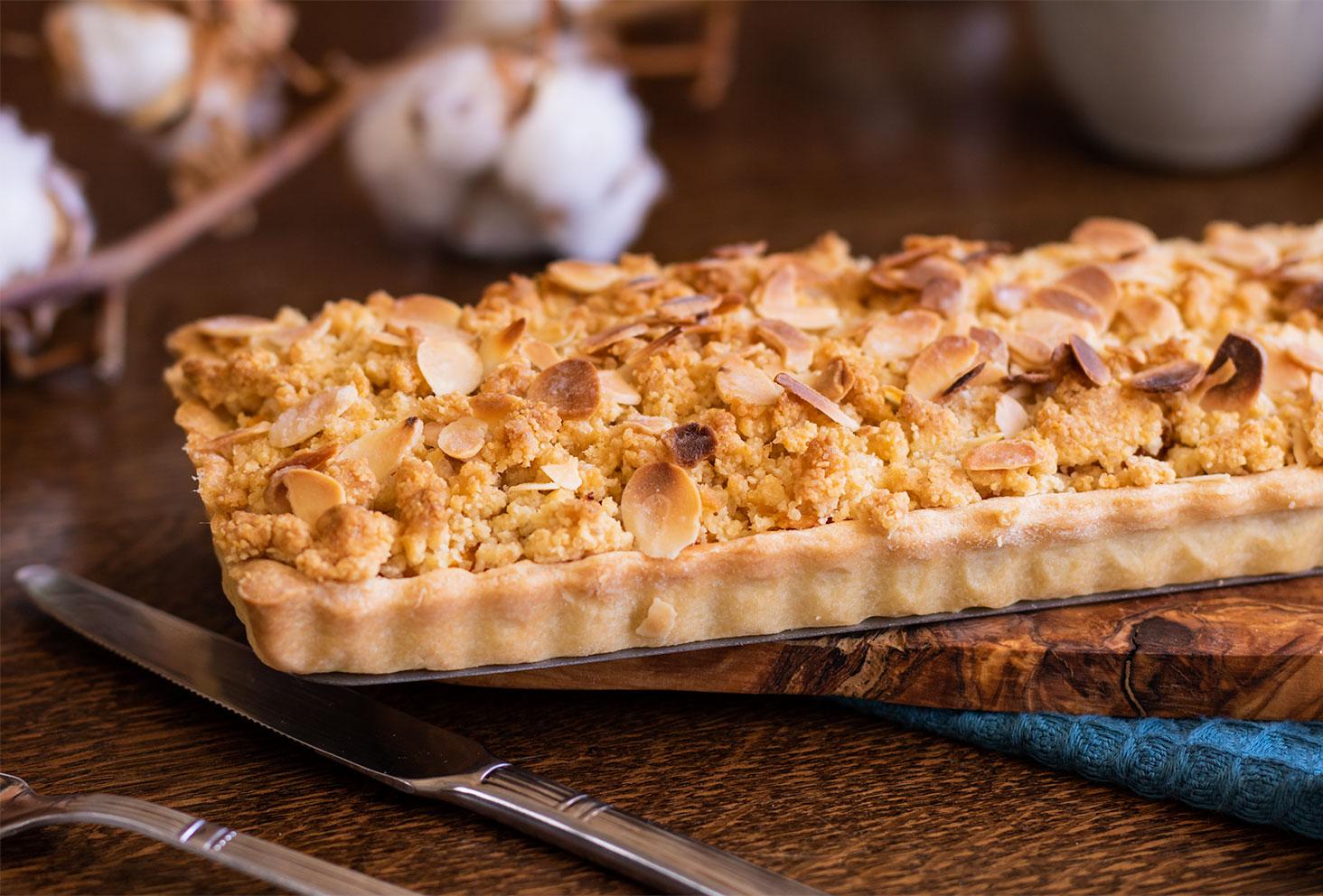 Zoom sur la texture du crumble et des amandes effilées de la tarte crumble aux pêches et amandes