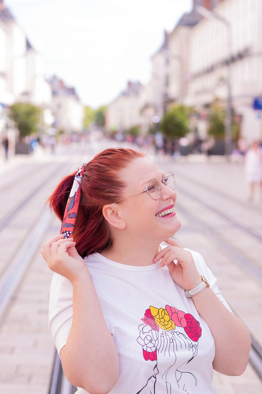 Une demi queue de cheval attachée avec un headband orange, au milieu d'une rue la main dans les cheveux avec le sourire, légèrement de profil