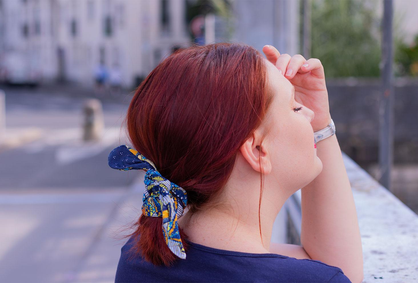 Zoom sur un bandeau bleu qui tient une queue de cheval basse, de profil accoudée à un pont
