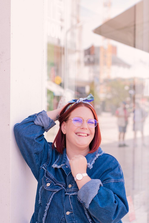 Contre la vitrine d'une boutique, une main à la veste et l'autre dans les cheveux, un headband bleu noué avec le sourire