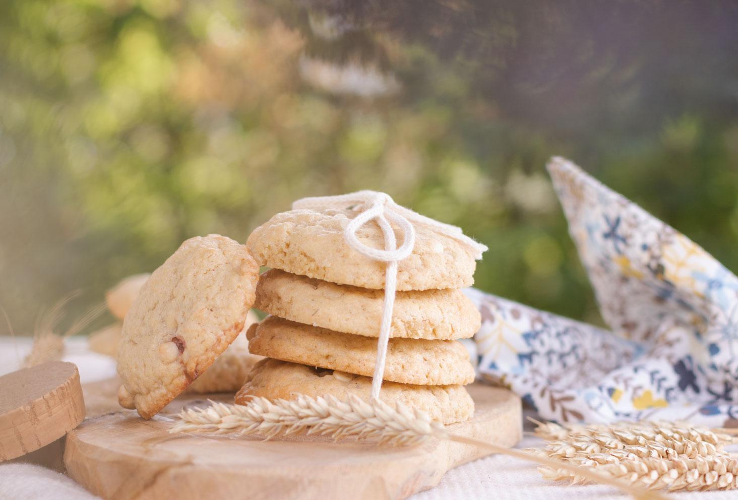 Un paquet de cookies fourrés à la fraise et à la purée de cacahuètes faits maison, posés sur une planche en bois à côté d'épis de blé