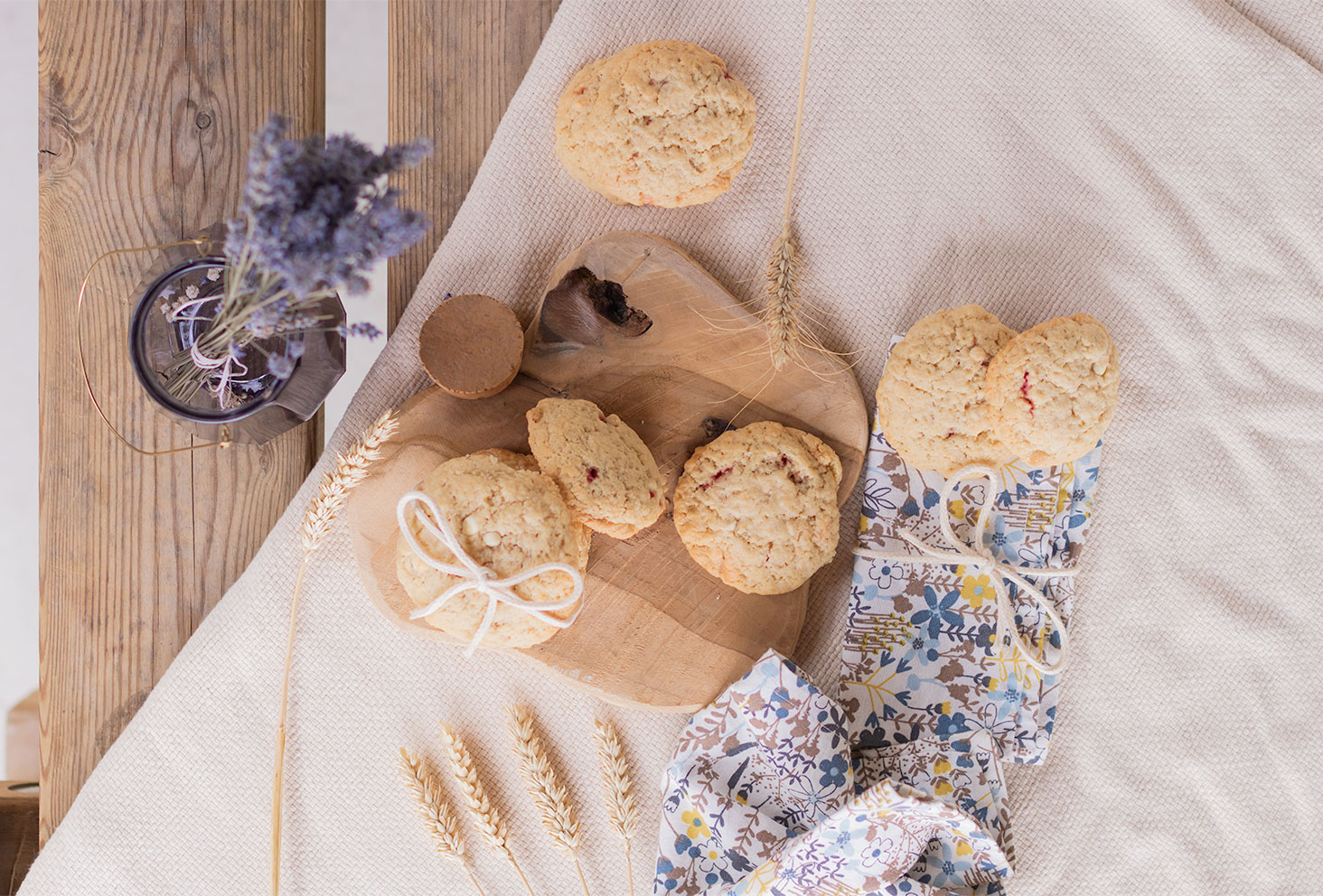 Des cookies fourrés à la fraise et à la purée d'oléagineux vu de haut sur une planche en bois et une table en bois