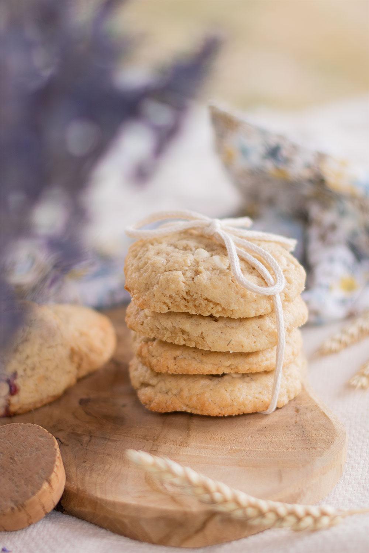 Des cookies fourrés à la cacahuètes et au chocolat blanc posés sur une planche en bois caché derrière un bouquet de lavande séché