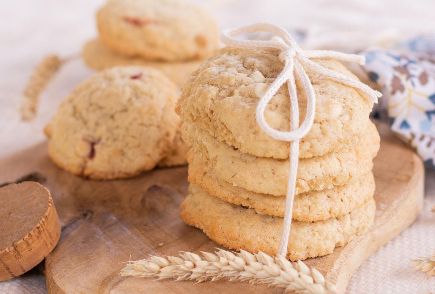 Zoom sur un paquet de cookies fourrés noués avec une ficelle, sur une planche en bois au milieu de blé