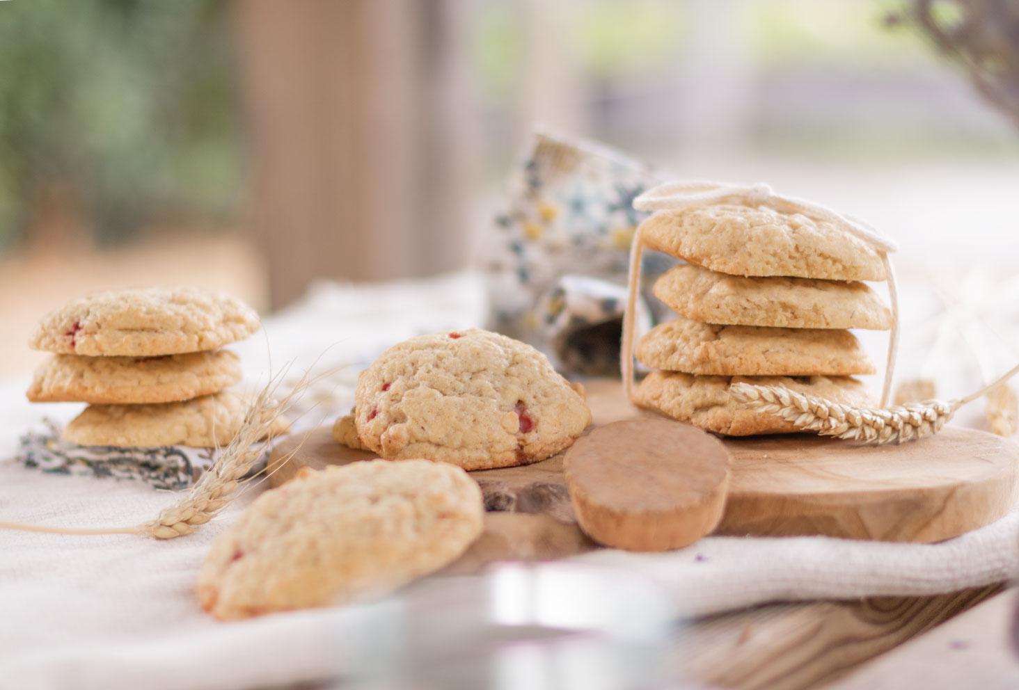 Plusieurs cookies fourrés à la fraise et aux oléagineux sur une planche en bois au milieu d'épis de blé séché