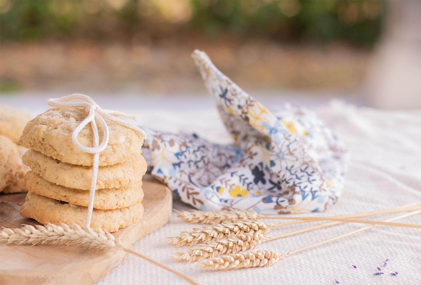 Des cookies fourrés au chocolat blanc, en pile sur une planche en bois