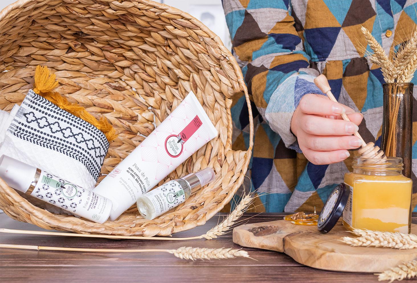 La gamme de produits Folies Royales dans un panier en osier, à côté d'un pot de miel et d'une cuillère de miel plongée dedans