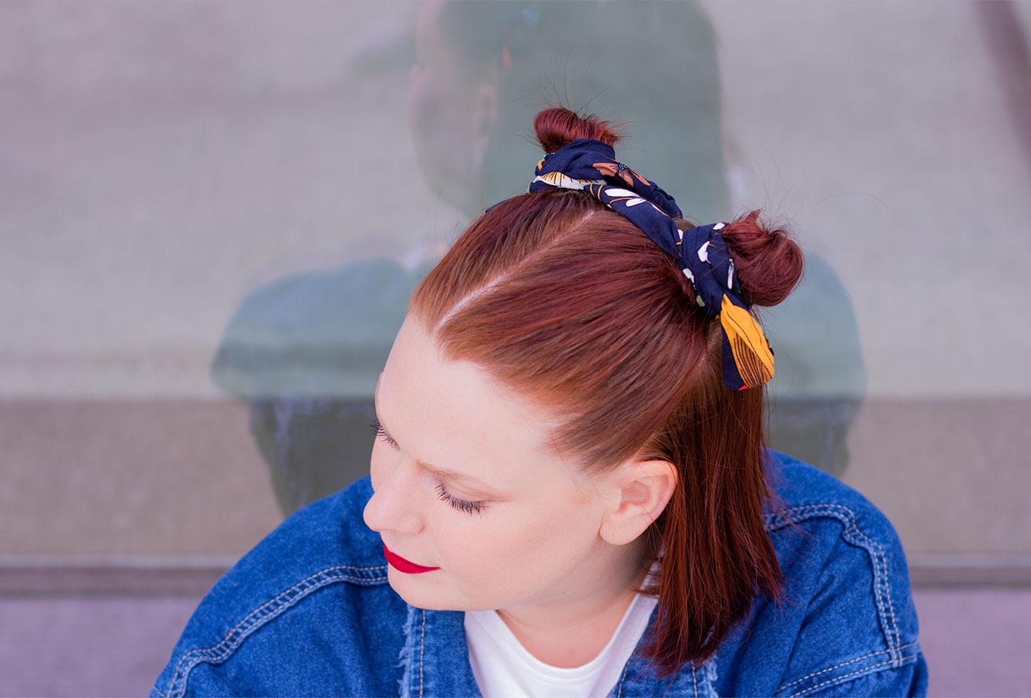 Des chignons sur la tête enroulé dans des headband bleus et jaune moutarde, la tête baissée vers le bas en veste en jean