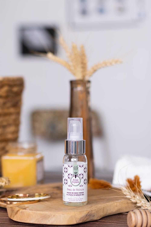 L'huile de soin visage de Folies Royales debout sur une planche de bois devant un bouquet de blé séché