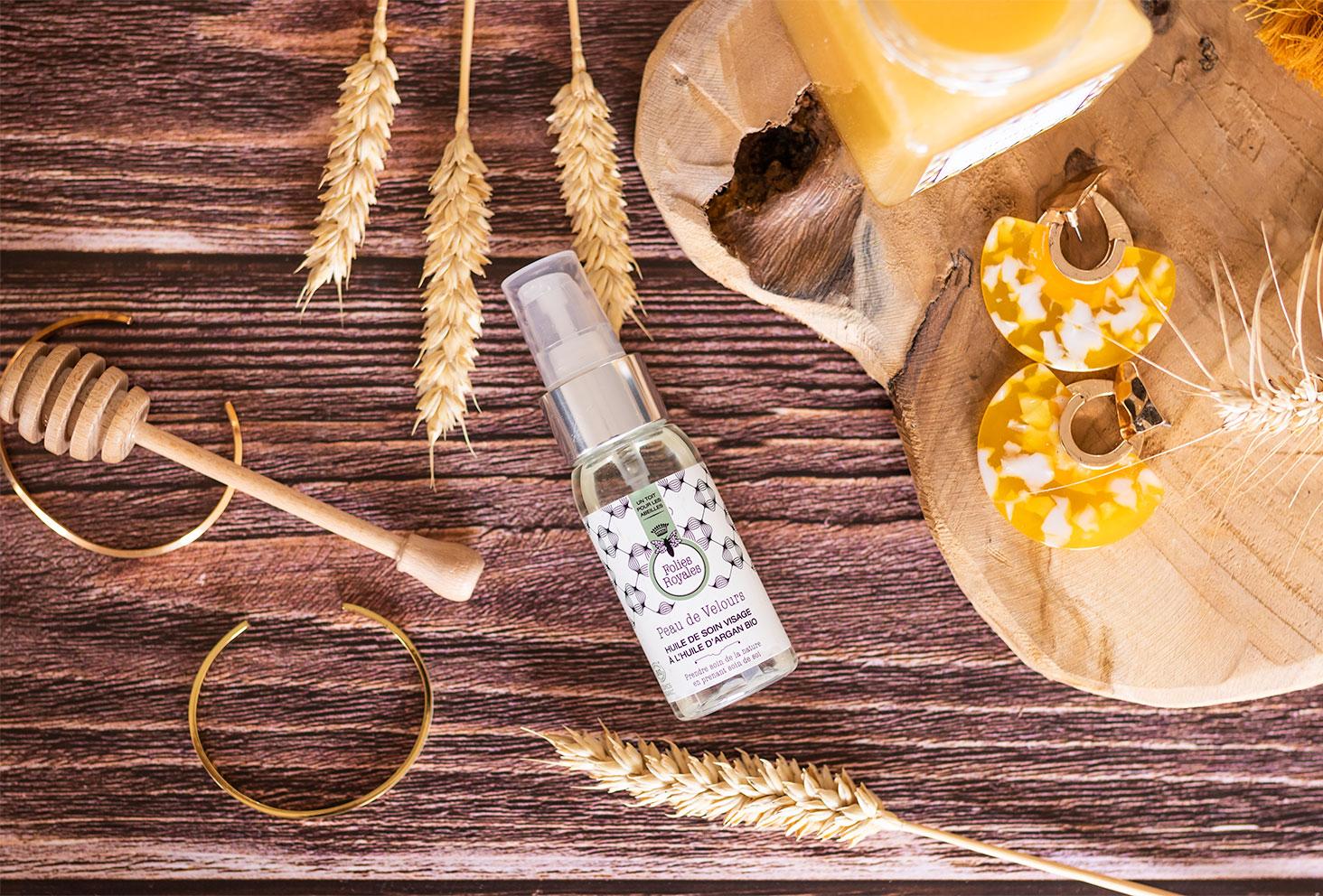 L'huile de soin visage vu de haut, posé sur un fond en bois, à côté s'une planche à découper au milieu de blé séché, de miel et de bijoux dorés