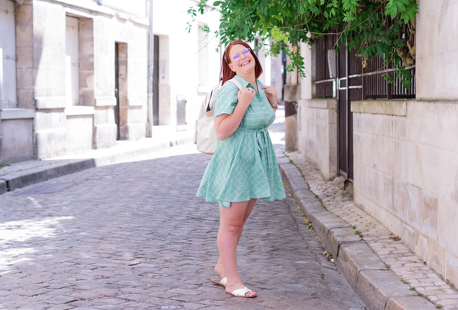 Dans la rue avec le sourire, en robe fluide verte SheIn, un sac à dos beige sur le dos pour la rentrée