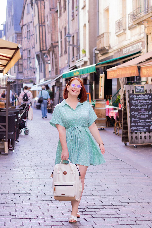 Dans la rue agitée, un sac à dos beige à la main, avec le sourire en robe verte fluide SheIn