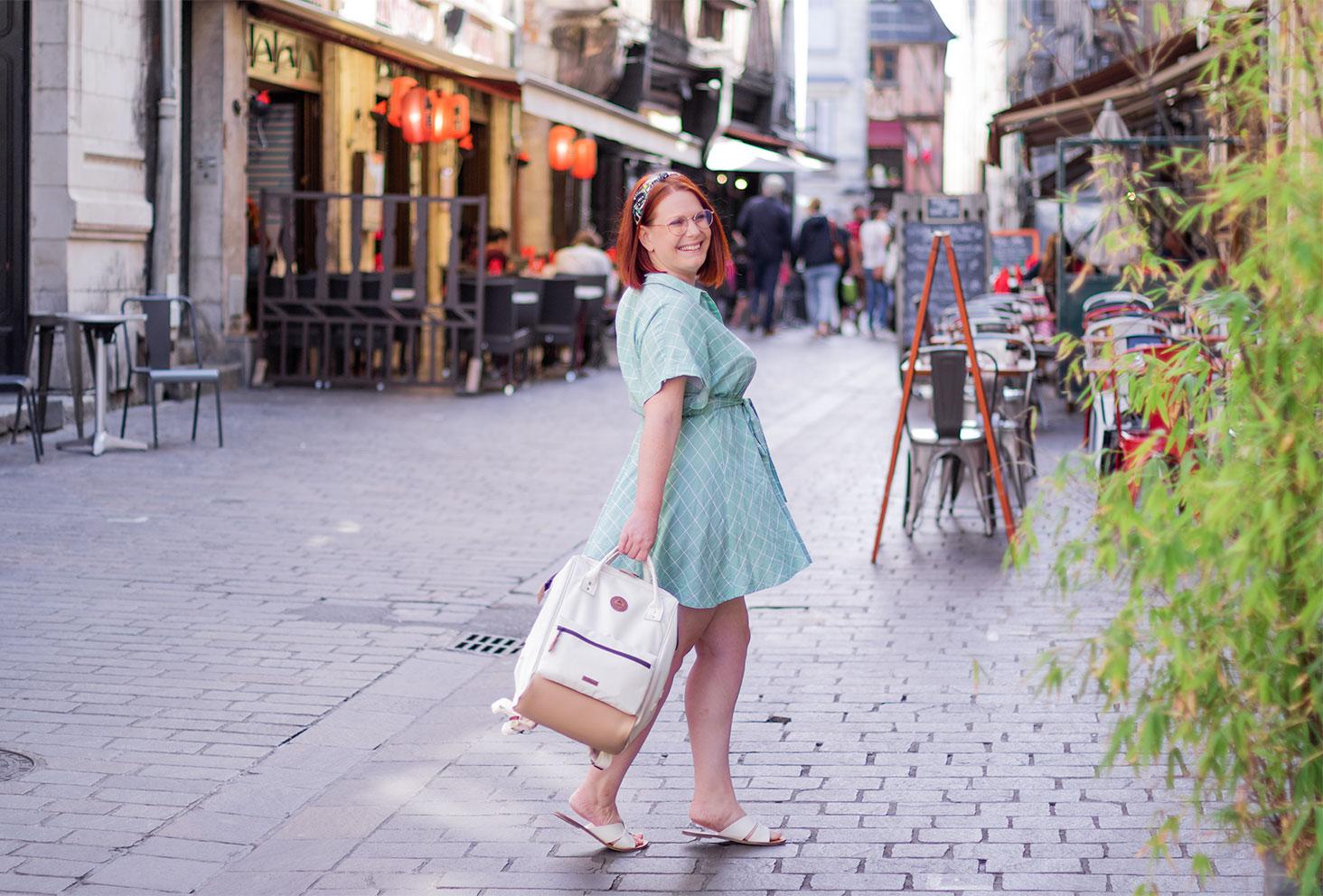 Un look pour la rentrée, au milieu d'une rue avec le sourire, en robe verte à carreaux et sac à dos Cabaïa tenu à la main