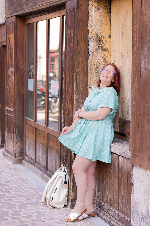 Le dos appuyé le long d'une façade en bois, avec le sourire et les bras croisés, en robe verte pâle un sac à dos posé aux pieds