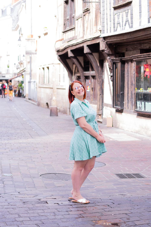 Au milieu d'une rue de profil, en robe chemise verte SheIn, avec le sourire