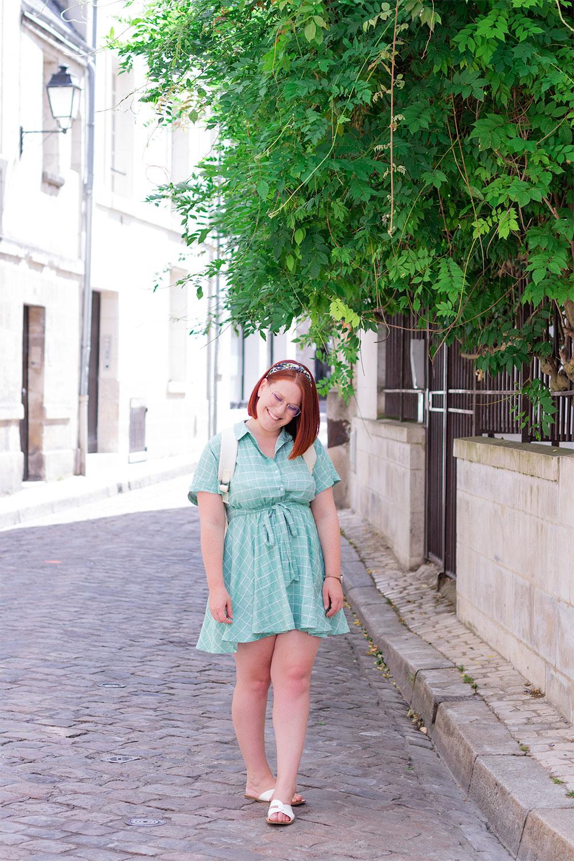 Look de rentrée avec un sac à dos sur le dos et une robe chemise verte, avec le sourire en train de marcher dans la rue