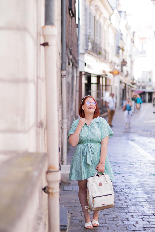 En train de marcher dans la rue, en robe fluide turquoise SheIn avec un sac à dos tenu à la main, en souriant