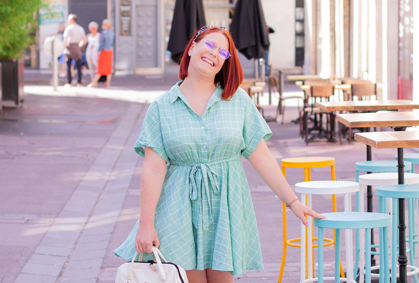En robe chemise à carreaux turquoise, appuyée à un tabouret haut de la même couleur que la robe, avec le sourire et un sac tenu à la main