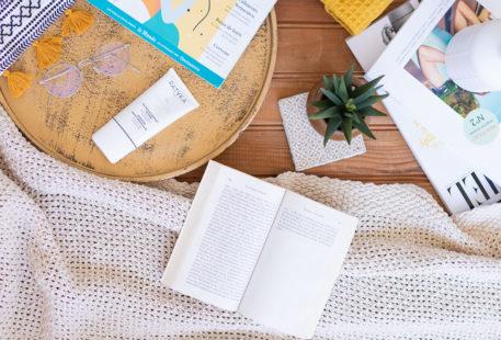 Un livre ouvert sur un plaid, des magazine, des lunettes de vue, une jolie plante, et le masque hydratant intense de Patyka