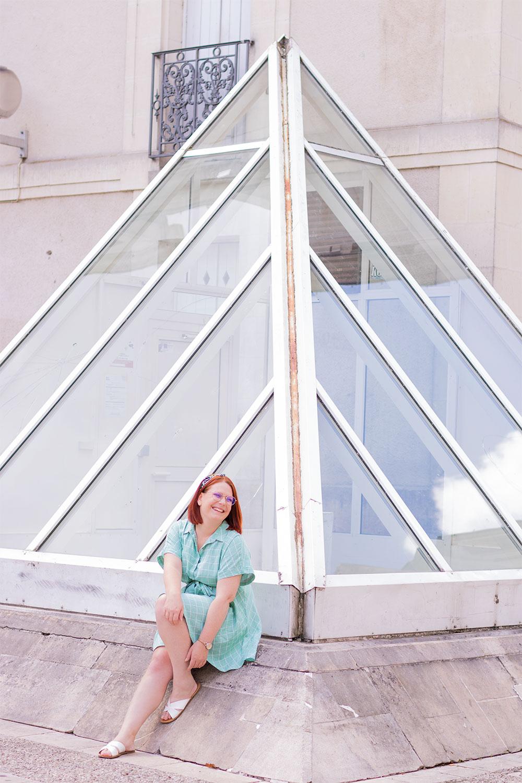 Assise devant une haute pyramide en verre avec le sourire, en robe fluide verte