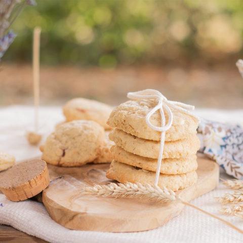 Des cookies fourrés aux morceaux de fraises et à la purée d'oléagineux, posés sur une planche en bois derrière un vase de lavande séchée