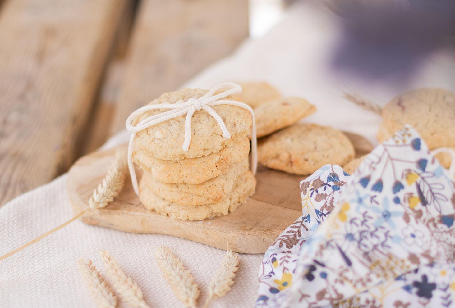 Des cookies sur une planche en bois, noués à l'aide d'une ficelle, fourrés aux fraises et aux oléagineux
