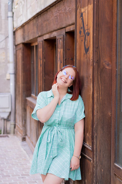 En robe cintrée verte, appuyée de profil à une façade en bois, avec le sourire une main dans le cou
