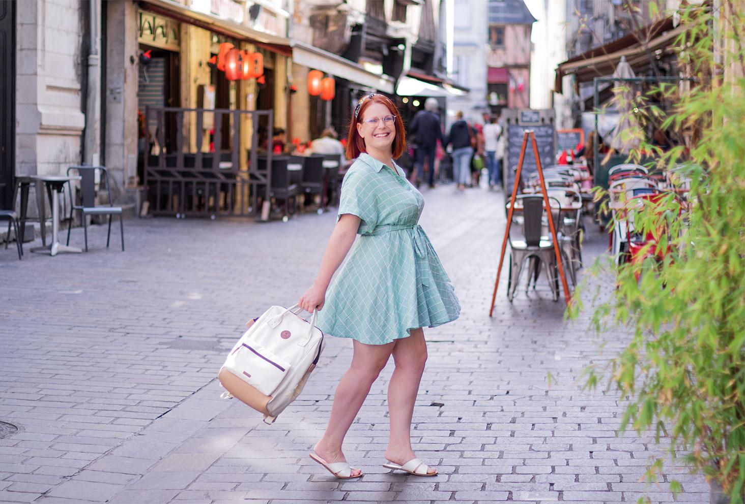 Avec le sourire au milieu de la rue, en train de marcher en robe verte fluide un sac à dos dans la main